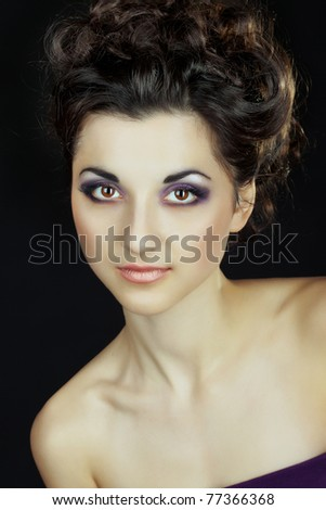 Portrait of a beautiful woman on a black background with make-up - stock photo