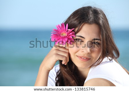Portrait of a beautiful woman on the beach with a pink flower with the sea in the background - stock photo