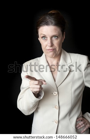 Portrait of a beautiful woman pointing and telling someone to quiet down. - stock photo