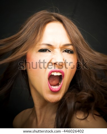 Portrait of a beautiful woman screaming on black background