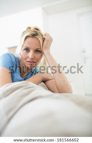 Portrait of a beautiful woman sitting in the living room at home