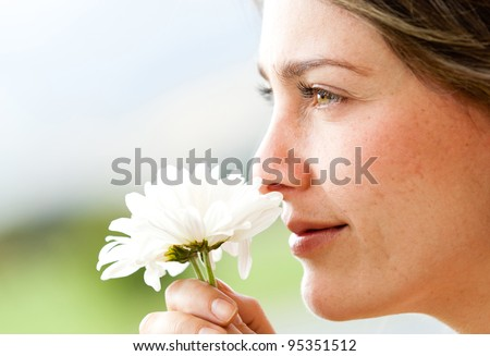 Portrait of a beautiful woman smelling a flower - stock photo