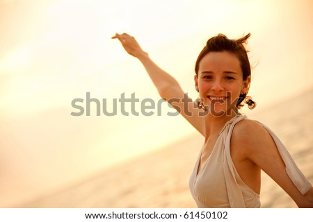 Portrait of a beautiful woman smiling at sunset outdoors - stock photo