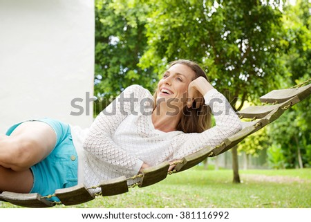 Portrait of a beautiful woman smiling on hammock outdoors - stock photo
