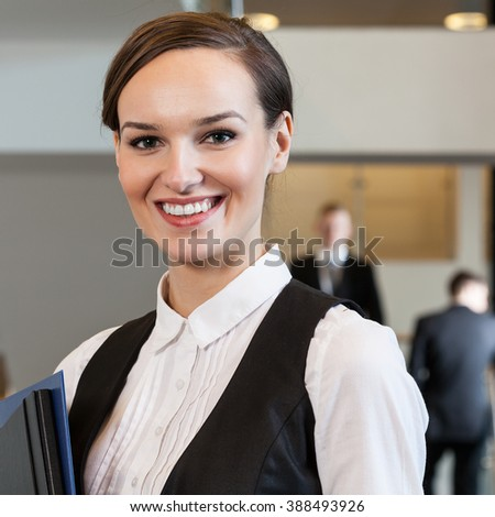 Portrait of a beautiful woman standing in business centre - stock photo