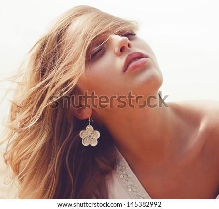 Portrait of a beautiful woman sunbathing on the beach - stock photo