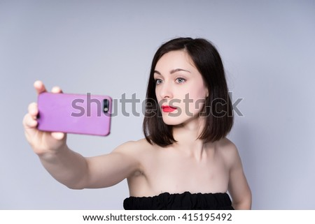portrait of a beautiful woman taking selfie in short brunette bob with neat clean hair on studio background
