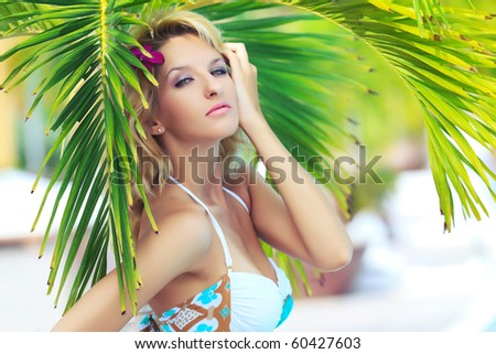 Portrait of a beautiful woman under palm tree - stock photo