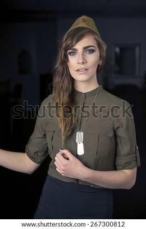Portrait of a beautiful woman wearing Soviet military hat and dog tags - stock photo