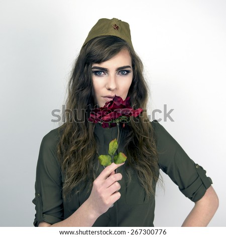 Portrait of a beautiful woman wearing Soviet military hat and holding a rose - stock photo
