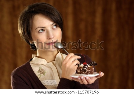 portrait of a beautiful woman with a cake in hand - stock photo