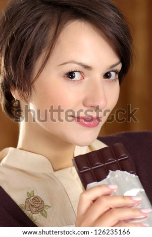 portrait of a beautiful woman with a chocolate bar in his hands - stock photo