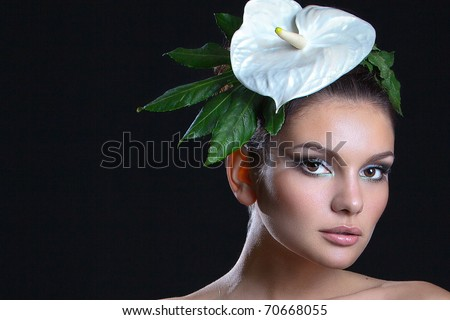 portrait of a beautiful woman with a flower on a dark background