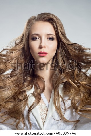 Portrait of a beautiful woman with a flowing hair in a white negligee