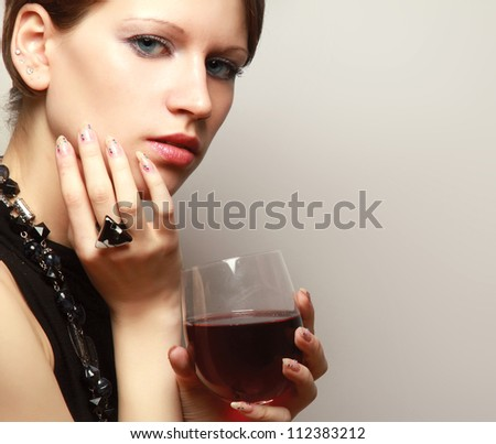 Portrait of a beautiful woman with a wineglass over the wall, isolated on grey - stock photo