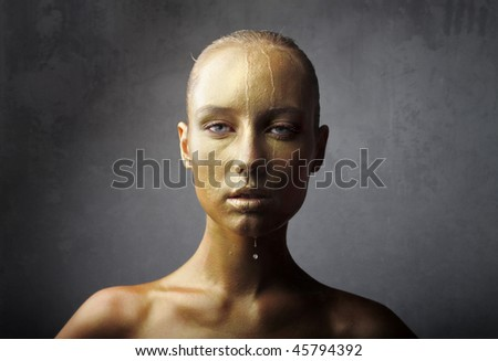Portrait of a beautiful woman with gold-colored visage - stock photo