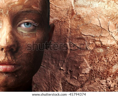 Portrait of a beautiful woman with her face covered with clay - stock photo