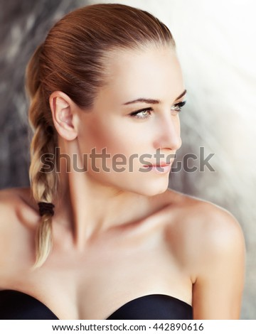 Portrait of a beautiful woman with natural makeup and stylish braid hairstyle looking aside, authentic beauty, fashion look of a gorgeous young model with perfect skin - stock photo