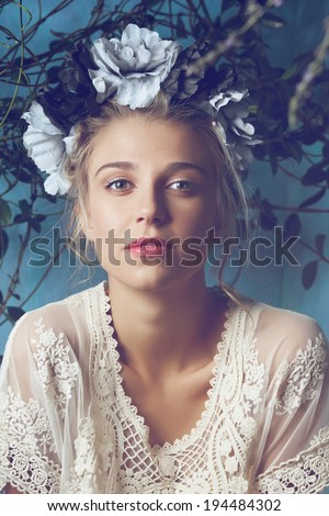 Portrait of a beautiful woman with natural makeup. Wearing silk flower headpiece on grunge plant background - stock photo