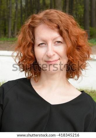 Portrait of a beautiful woman with red curly hair in a black blouse - stock photo