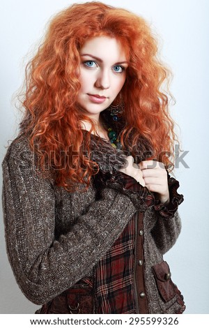 portrait of a beautiful woman with red curly hair in knitted winter clothes - stock photo
