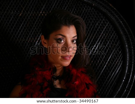 Portrait of a beautiful woman with red feather-boa draped around her neck - stock photo
