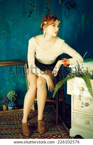 portrait of a beautiful woman with red hair in braided hairstyle. wearing leather shorts and lace top on grunge painted background  - stock photo
