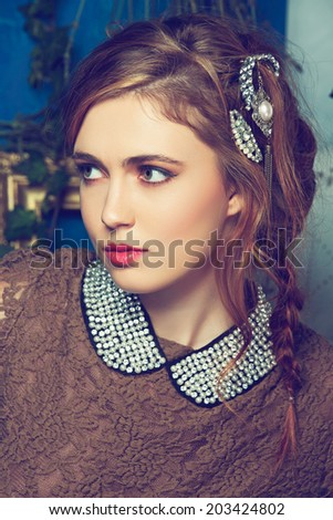 portrait of a beautiful woman with red hair in curly braided hairstyle. wearing a romantic lace dress and pearl collar on grunge wall background  - stock photo