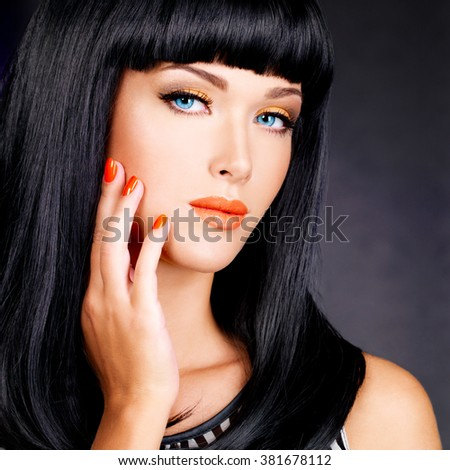 portrait of a beautiful woman with red nails and glamour makeup and  long black hairs -   at studio - stock photo