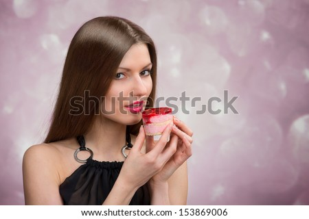 Portrait of a beautiful woman with the cake on abstract background - stock photo