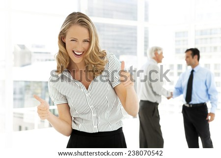 Portrait of a beautiful woman with thumbs up and partners shaking hands on background - stock photo