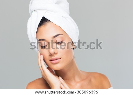 Portrait of a beautiful woman with towel on head on gray background - stock photo