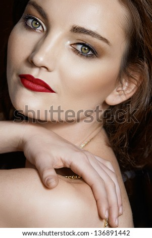 Portrait of a beautiful 30 year old brunette woman with green eyes wearing evening make-up with dark red lipstick - stock photo