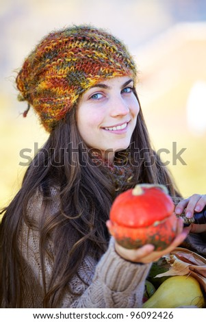 Portrait of a beautiful 20 year old holding a small pumpkin outdoor. - stock photo