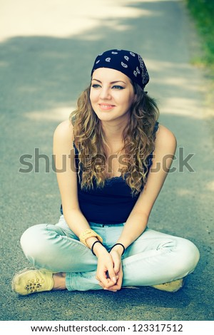 Portrait of a beautiful 20 year old woman enjoying a summer day outdoor. - stock photo