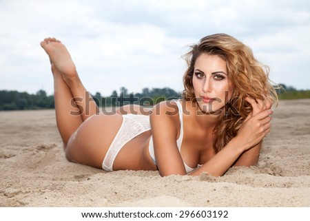 Portrait of a beautiful young adult attractive sexy and sensuality pretty brunette woman wearing white lingerie on the beach - stock photo