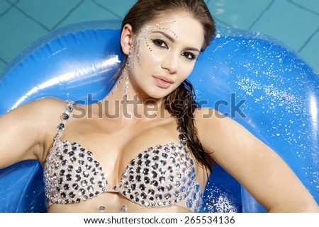 Portrait of a beautiful young adult attractive sexy and sensuality pretty brunette woman with damond make up in swimmingpool - stock photo