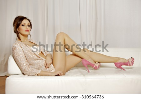 Portrait of a beautiful young adult attractive sexy and sensuality pretty female brunette woman posing in pink lingerie on the white couch - stock photo