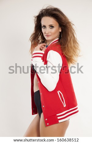 portrait of a beautiful young adult sensuality brunette cheerleader woman girl in black lingerie, white and red baseball jacket isolated on white background - stock photo