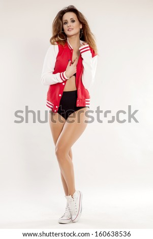 portrait of a beautiful young adult sensuality brunette cheerleader woman girl in black lingerie, white and red baseball jacket isolated on white background