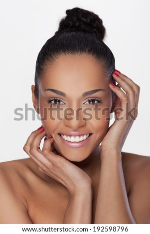 Portrait of a beautiful young African woman smiling, with fingers on her face. Beauty concept - stock photo