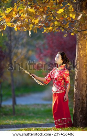 Portrait of a beautiful young asian woman with fan - stock photo
