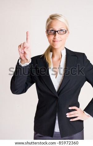 Portrait of a beautiful young blond business pointing upwards - stock photo