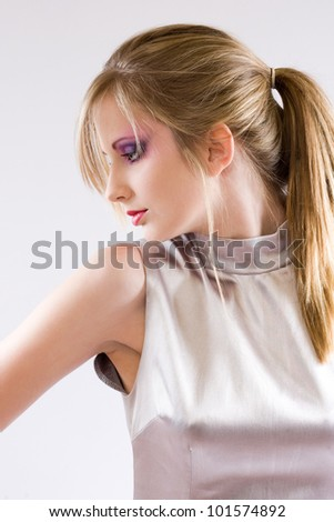 Portrait of a beautiful young  blond in retro style silver dress - stock photo