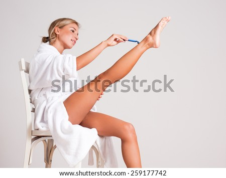 Portrait of a beautiful young blond shaving her legs. - stock photo