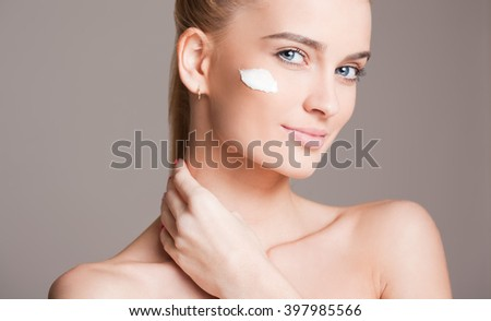 Portrait of a beautiful young blond woman using skin care cosmetics.