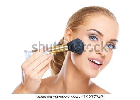 Portrait of a beautiful young blonde applying makeup to her face - stock photo
