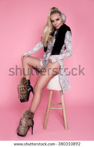 portrait of a beautiful young blonde fashion model with a long ponytail, dressed with winter sweater collar fox,earmuffs sitting on a chair on a pink background sensual, sexy makeup with sensual eyes - stock photo