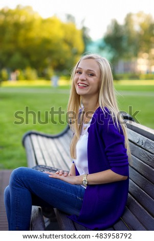Portrait of a beautiful young blonde girl in the park. She is sitting on the wooden bench