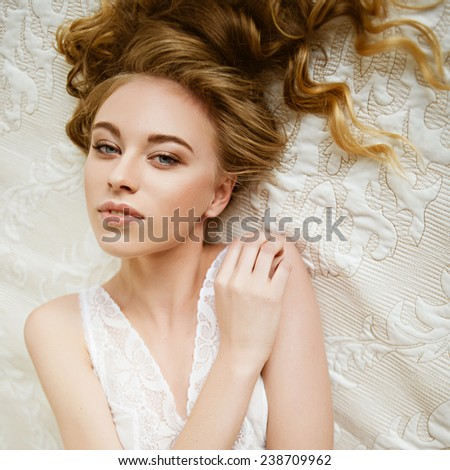 Portrait of a beautiful young blonde girl lying on white bed in lingerie